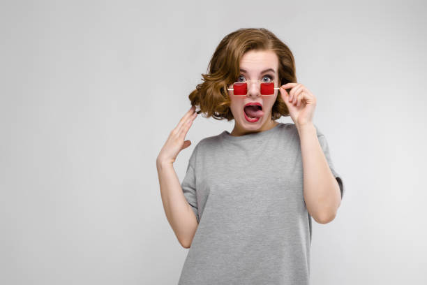 charming young girl in a gray t-shirt on a gray background. girl in red square-eyed glasses. - kids kiss embarrassed foto e immagini stock