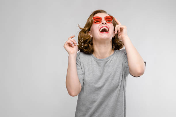 charming young girl in a gray t-shirt on a gray background. happy girl in red glasses. the girl laughs - kids kiss embarrassed foto e immagini stock