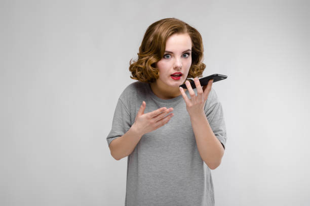 charming young girl in a gray t-shirt on a gray background. the girl speaks by phone - kids kiss embarrassed foto e immagini stock