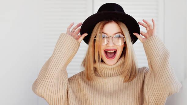 Chica encantadora con un sombrero elegante y gafas. Mujer joven vistiendo frenillos y sonriendo - foto de stock
