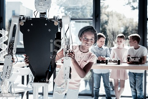 istock Charming young lady posing with robotic machine 939692898