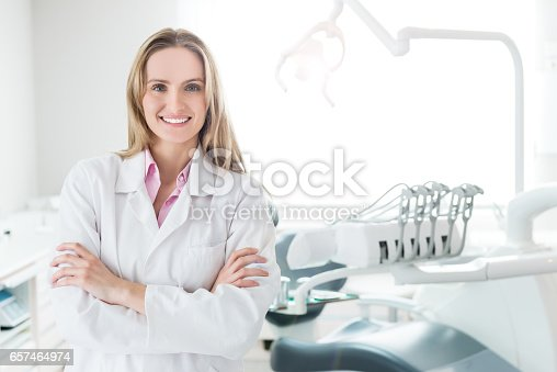 Horizontal color front view image of beautiful medical expert standing with crossed arms in dental clinic office. Female doctor wearing white uniform,smiling and looking at camera.