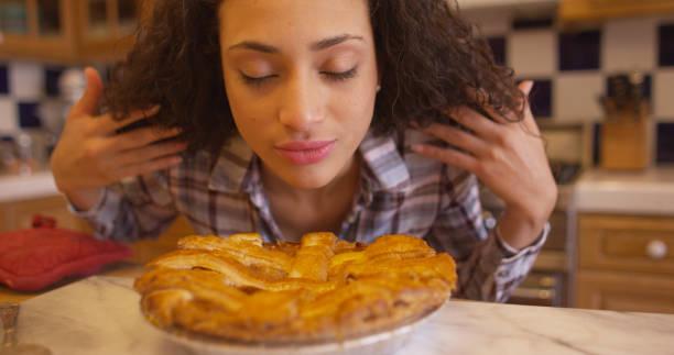 charmiga unga blandade etniska kvinna luktar äppelpaj. - food woman to smell bildbanksfoton och bilder