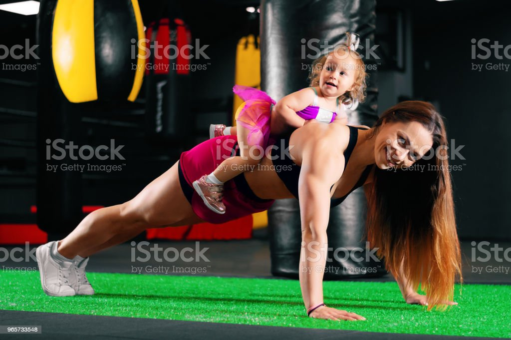 Charming young mother is wringing out with her daughter. The girl is sitting on her mother's back. - Royalty-free Activity Stock Photo