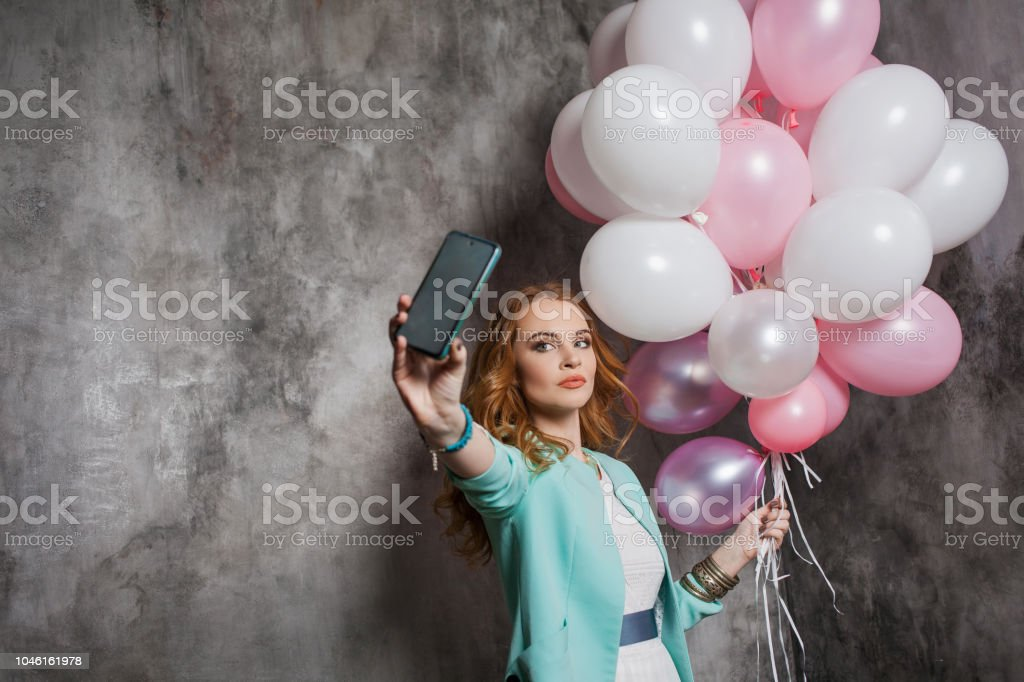Charming young redhead girl with pink balloons, make a selfie stock photo