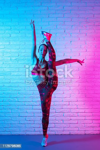 Charming young slim gymnast woman in sports clothing stretching on brick wall in neon lights.