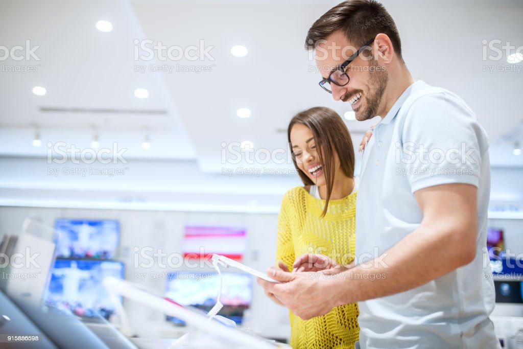 Charming young smiling love couple looking on a tablet while buying in a tech store. stock photo