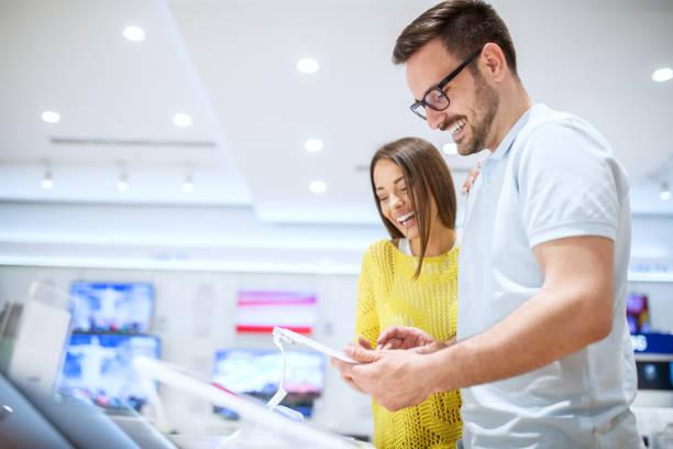 charmante junge lächelnde liebespaar auf der suche auf einem tablet beim kauf im ladengeschäft tech. - freizeitelektronik stock-fotos und bilder