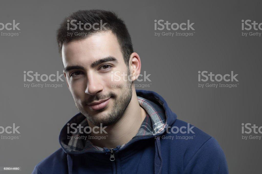 Charming young unshaven man smiling at camera stock photo