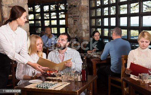 Charming young waiter receiving order from guests in country restaurant