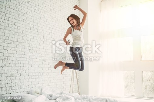 Happy young woman in earphones is listening to music with smart phone, jumping on bed, singing and smiling