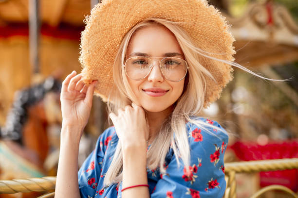 Charming young woman in hat near carousel stock photo