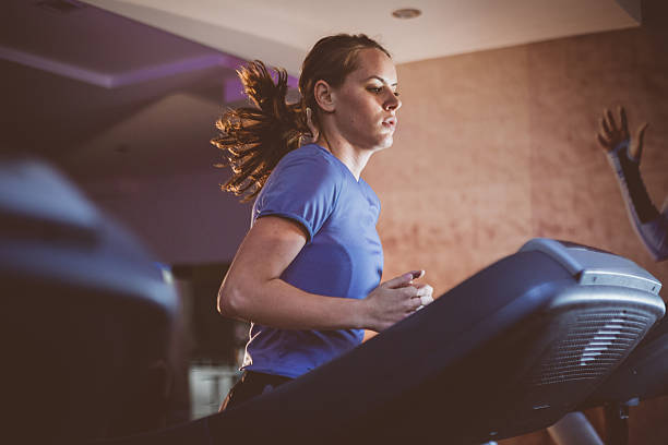 Charming Young Woman is Running Treadmill in Gym stock photo