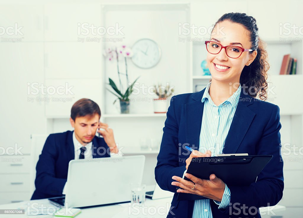 charming young woman manager holding cardboard in office - foto de stock