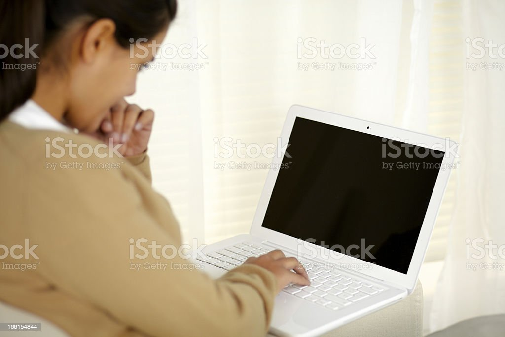 Charming young woman reading on laptop screen royalty-free stock photo