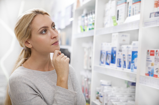 istock Charming young woman shopping at pharmacy 1164338427