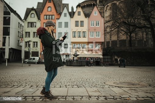Charming young woman using mobile phone in the city street in Germany