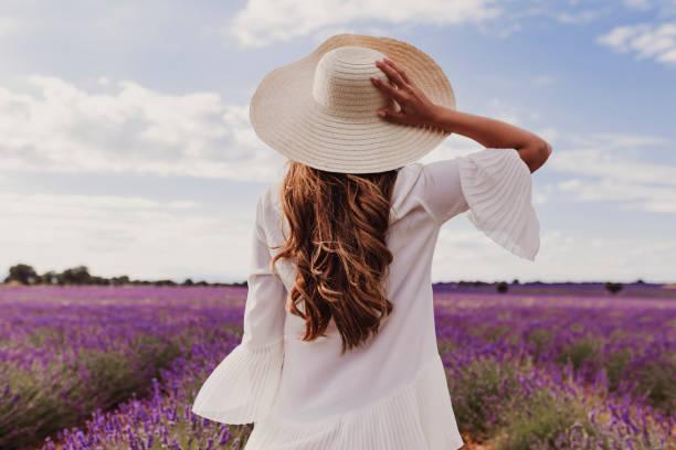 gün batımında mor bir lavanta alanında bir şapka ve beyaz elbise ile büyüleyici genç kadın. lifestyle açık havada. geri görünüm - beyaz elbise stok fotoğraflar ve resimler