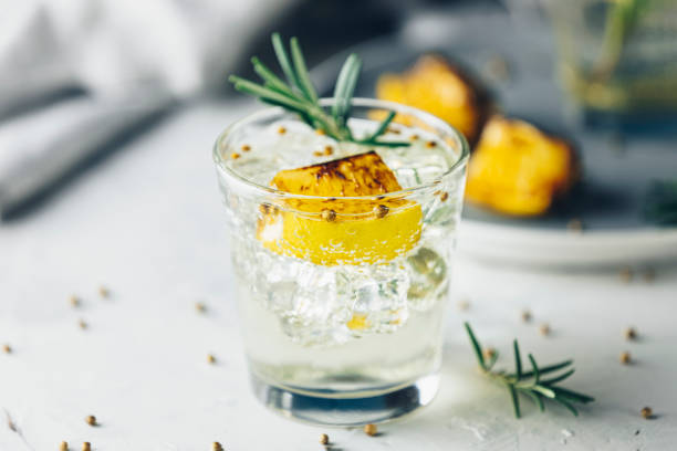 Charred Lemon, Rosemary and Coriander Gin and Tonic is a flavors are perfectly balanced refreshing cocktail. on light background, close up. Summer drinks and alcoholic cocktails stock photo