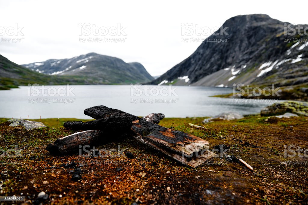 Charred peaces of timber used for a camp fire in the mountains of norway with a lake in the background stock photo