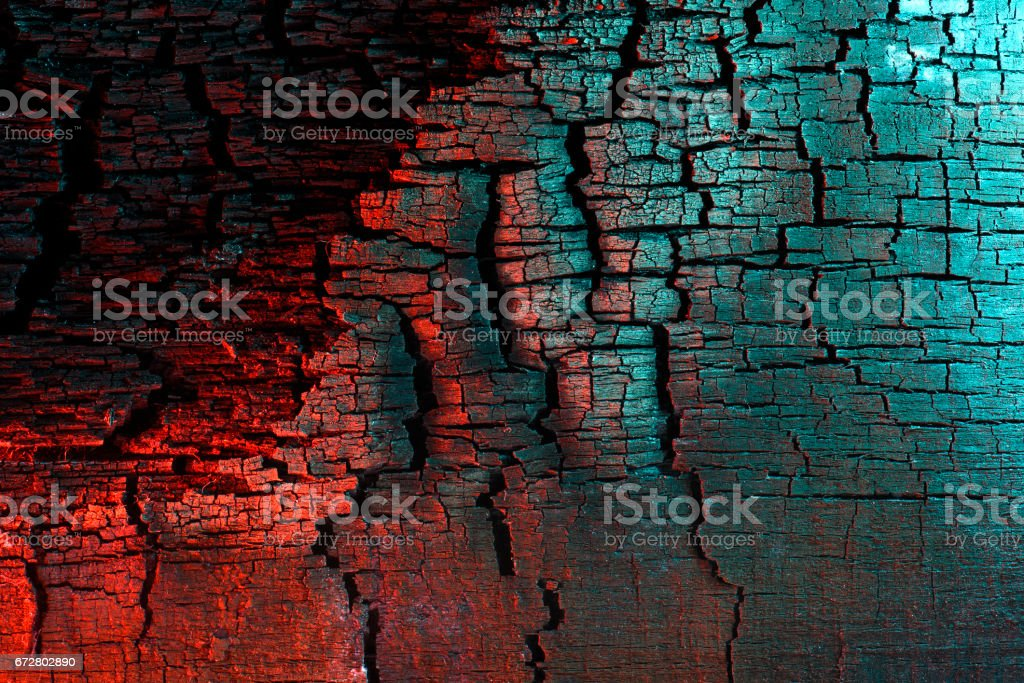 Charred wood texture, painted with light, red and turquoise. – Foto