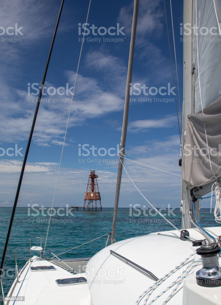 Charter catamaran approaches a reef lighthouse off the coast of the Florida, United States stock photo
