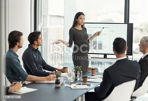 Cropped shot of a pregnant businesswoman giving a presentation on a monitor to colleagues in an boardroom