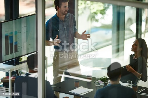 Shot of an executive leading a digital presentation to colleagues in a glass boardroom