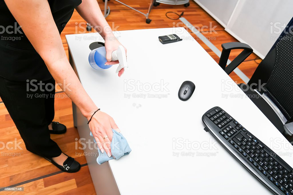 Charwoman cleaning a desk in an office