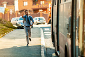 Young casual Businessman with backpacj and book Running To Catch Bus Stop during summer day.