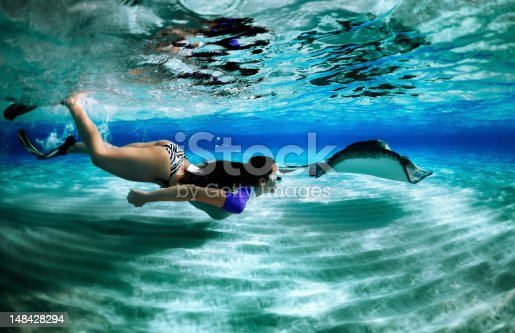 Woman snorkeling with a stingray in the sea.