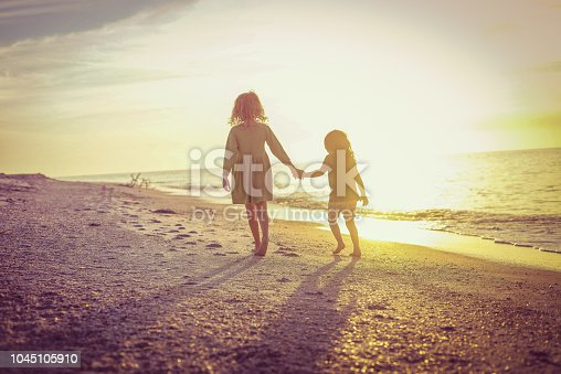 Little girls, sisters or friends, 4 and 7 years old hold hands on an idyllic deserted beach in paradise, walking toward the setting evening sun. Freedom, nature, childhood, family and friendship. A heartwarming moment