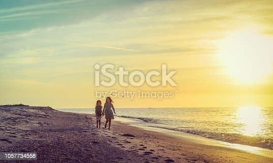 Little girls, sisters or friends, 4 and 7 years old hold hands on an idyllic deserted beach in paradise, walking and smiling with the  the setting evening sun behind them. Freedom, nature, childhood, family and friendship. A heartwarming moment