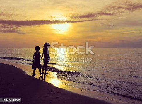 A breathtaking beautiful sunset over the ocean on the West Coast of Florida. Two children in silhouette run, play, and enjoy freedom, dance, frolic and childhood. tranquil ocean and idyllic pastel horizon, nature at it's finest and we feel the joy and exuberance of kids at play in an idyllic setting
