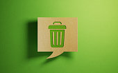 Chat bubble made of recycled paper on green background. There is a trash bin icon on chat bubble. Horizontal composition with copy space.