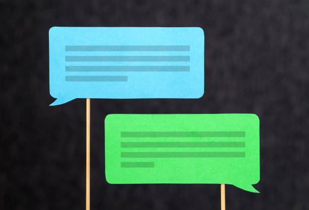 2 chat bubbles and speech balloons having discussion. Modern communication and conversation concept. Mobile and smartphone communication design made from cardboard and wooden stick. stock photo