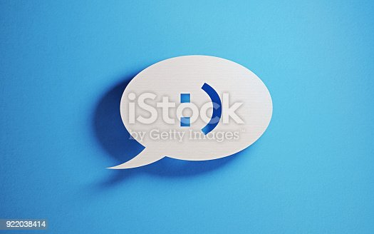 istock Chat Concept - White Chat Bubble With Happy Face Over Blue Background 922038414