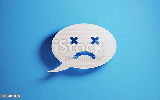 istock Chat Concept - White Chat Bubble With Sad Face Over Blue Background 922561626