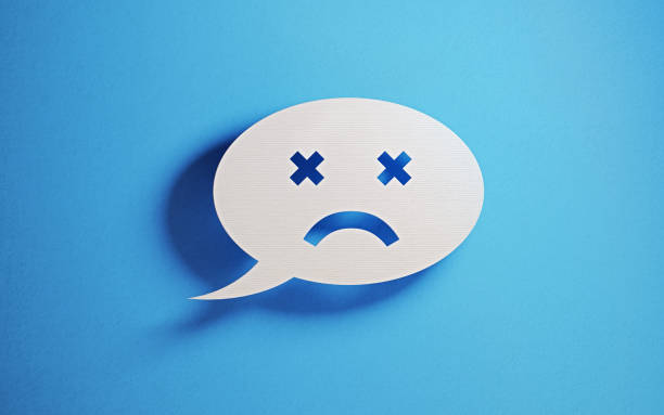 Chat Concept - White Chat Bubble With Sad Face Over Blue Background White chat bubble with sad face emoticon over blue background. Horizontal composition with copy space. Great use for online messaging concepts. negative emotion stock pictures, royalty-free photos & images