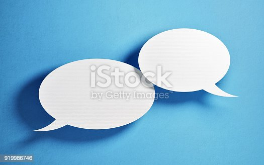 istock Chat Concept - White Chat Bubbles Over Blue Background 919986746