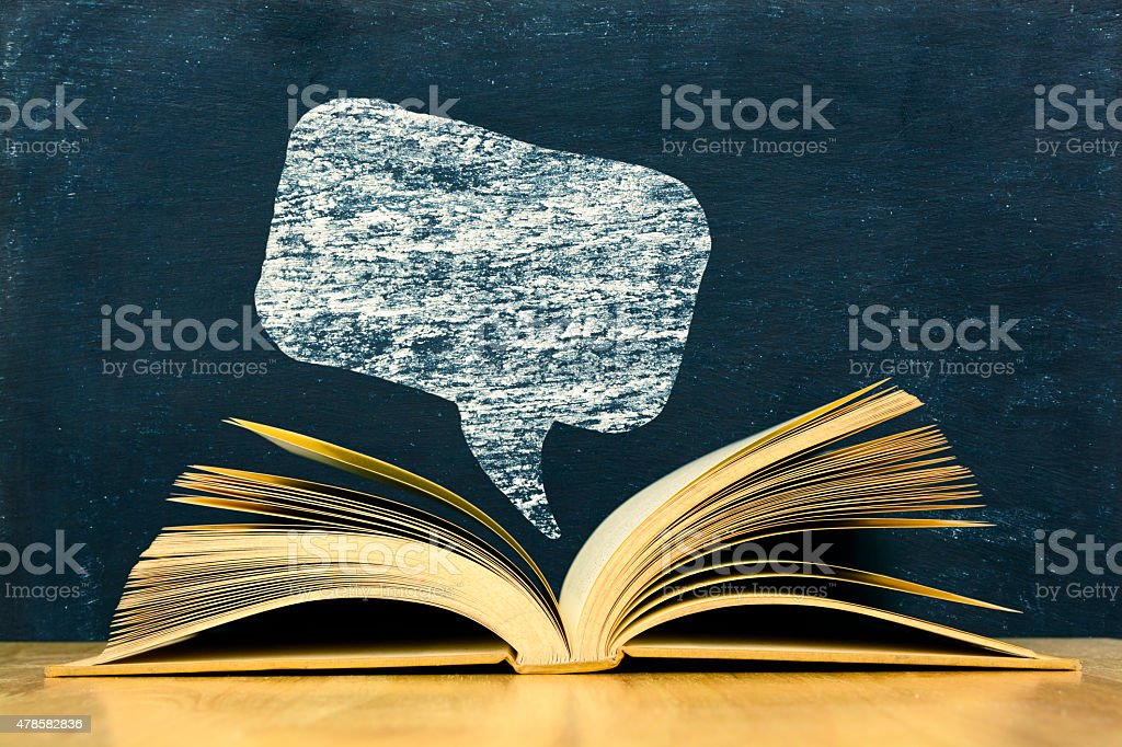 Chat symbol above vintage old book on blackboard background stock photo