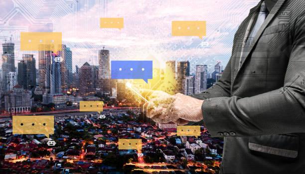 chatbot et internet du concept des choses. double exposition de circuit électrique graphique, technologie chat bot boîte de dialogue. homme d'affaires conviennent à la main en utilisant le téléphone intelligent avec le fond de la ville. - chatbot photos et images de collection