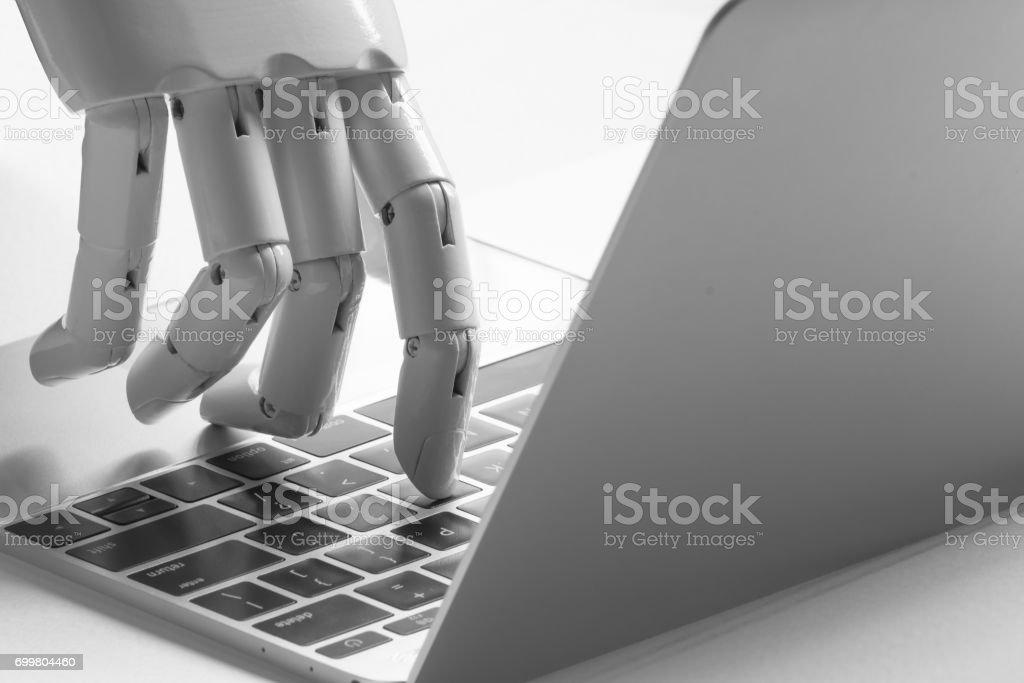 Chatbot , artificial intelligence , robo advisor , robotic concept. Robot finger point to laptop button. stock photo