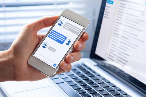 Conversa de chatbot na interface de app de tela smartphone com a tecnologia de inteligência artificial, fornecendo informações, mão pessoa segurando o telefone móvel e suporte ao cliente de assistente virtual - foto de acervo