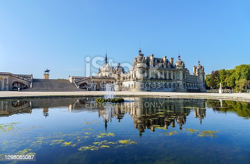 istock Chateau de Chantilly with reflection in a pond - France 1298085087