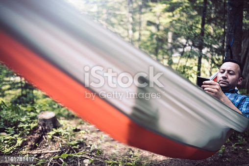 Man alone in the forest using phone while relaxing in a hammock