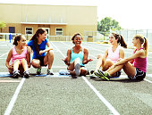 A group of friends sit on the track and discuss their lives.