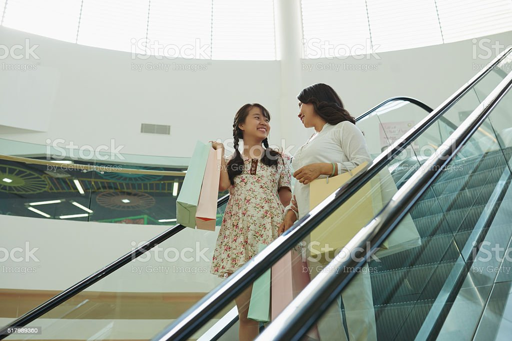 Chatting on escalator stock photo