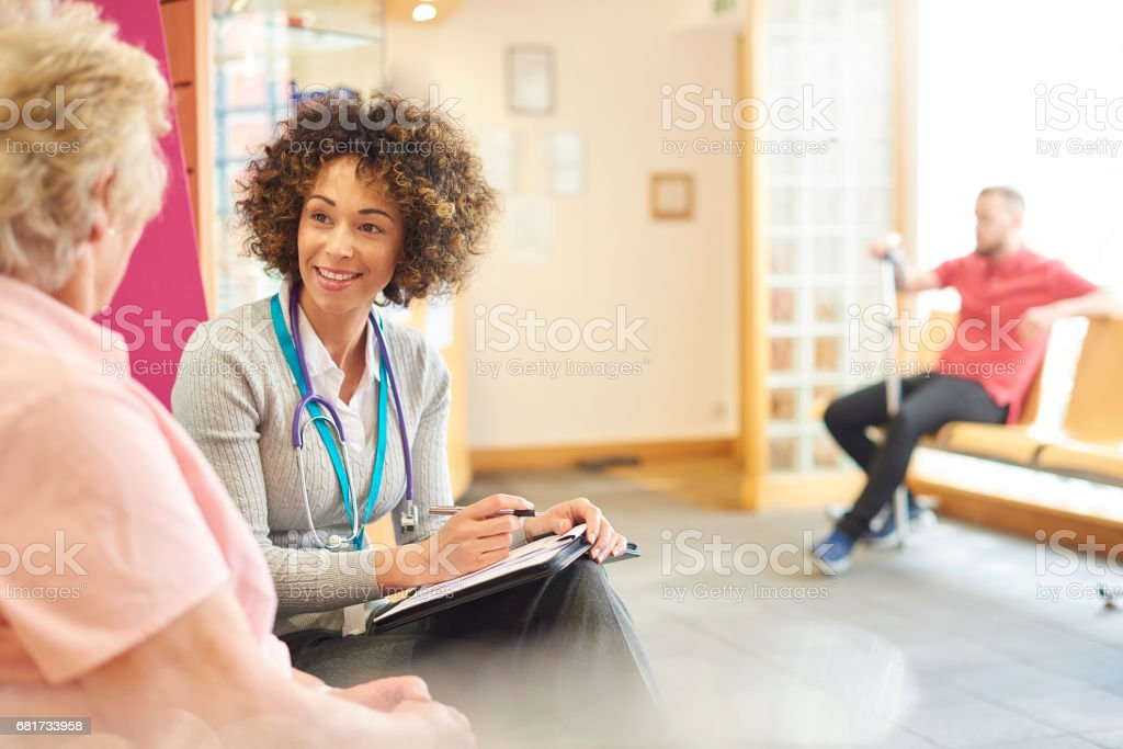 Chatting to senior patient in the waiting room stock photo
