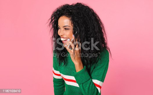 909457386istockphoto Chatting with a friend. Splendid African ethnic woman in a green sweatshirt with white and red stripes is holding a smartphone near her left ear and laughing while talking with someone. 1182103410